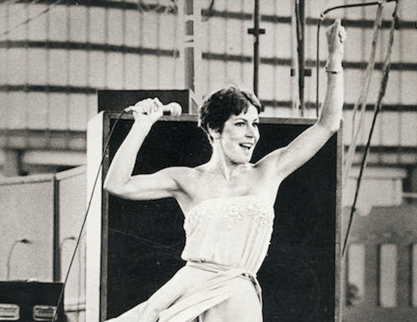 a black and white image of Helen Reddy performing in the 1970s