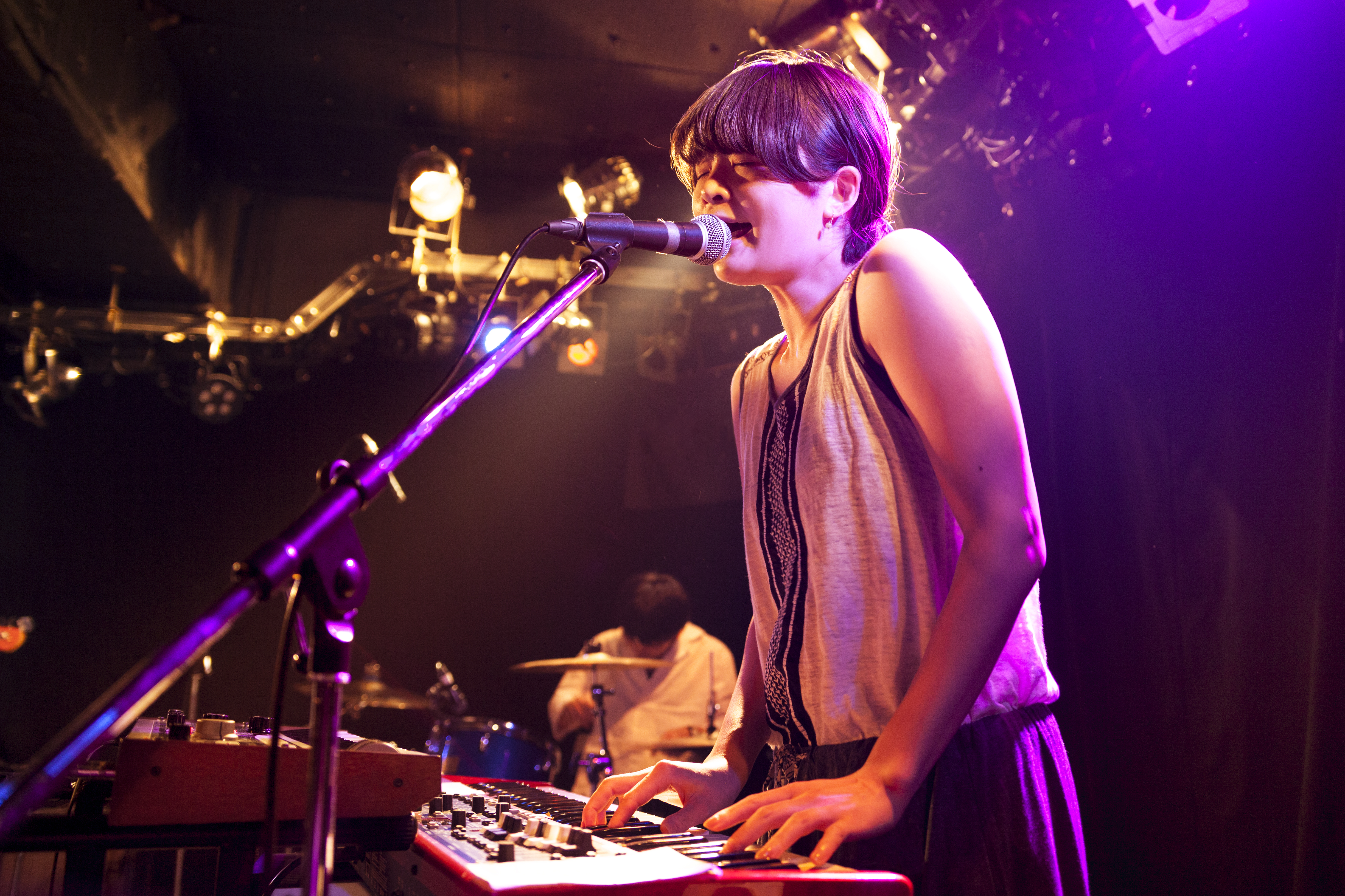 Woman plays keyboard live on stage and sings into microphone
