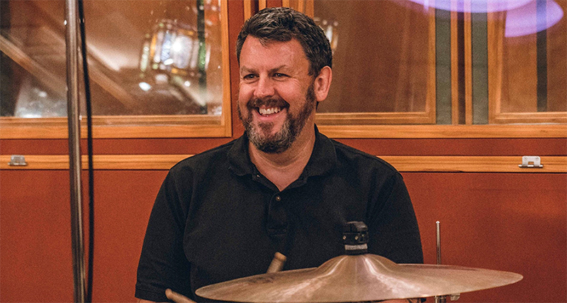 Music producer Greg Haver sits by a drum kit