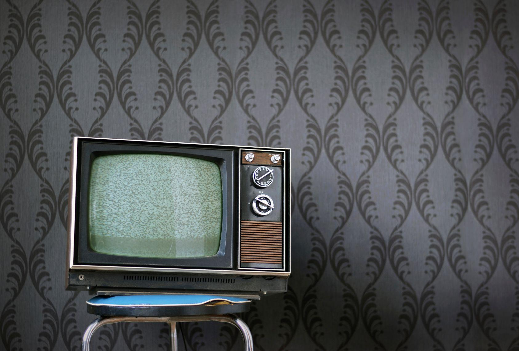 A retro looking TV in front of wallpaper