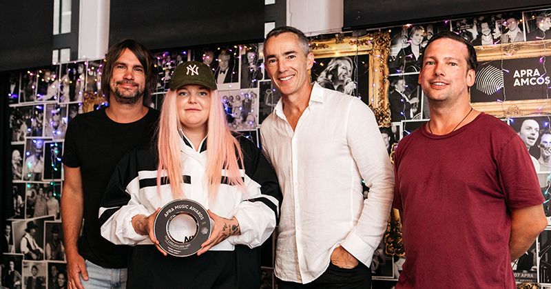 Artist Tones and I stands with her managers Regan Lethbridge and David Morgan, and APRA AMCOS CEO Dean Ormston holding a black trophy.