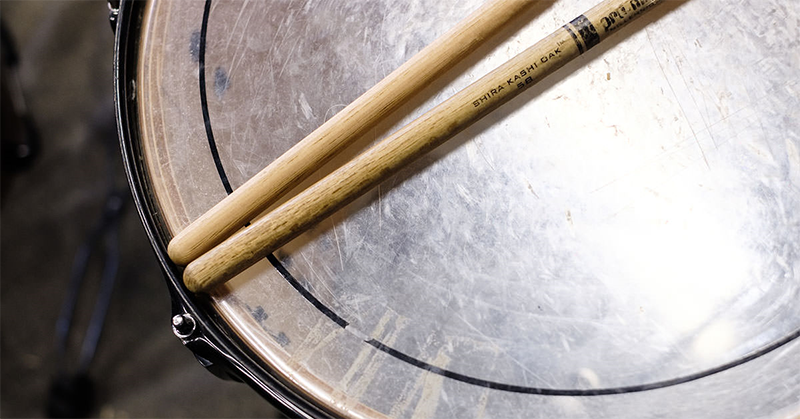 A pair of drum sticks sit on top of a snare drum