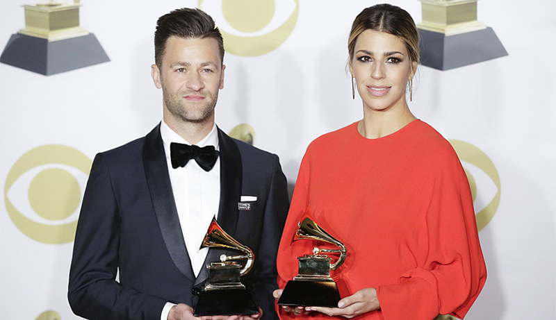 Ben Fielding wearing a tuxedo and Brooke Ligertwood in a red dress stand together holding their grammy trophies