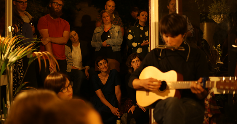 The band Big Smoke playing guitar and harmonica at a Parlour Gig with an intimate audience