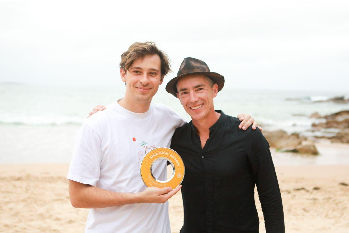 Harley Streten aka Flume stands on a beach holding his Billions award with Dean Ormston