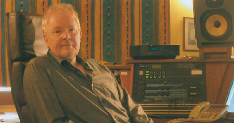 A faded photo of Graeham Goble sitting in a chair in a studio, with some mixing equipment and a speaker behind him