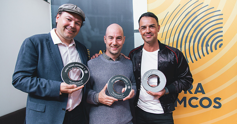 Jake Mason, Ivan Khatchoyna and Lance Ferguson  stand in front of an APRA banner with their Billions List trophies
