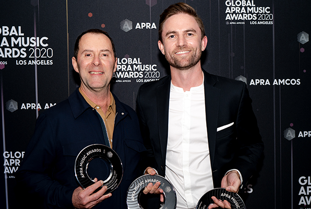 Joel Little and Sony/ATV Music Publishing's MD Damian Trotter stand in front of a media wall holding three black disk trophies.