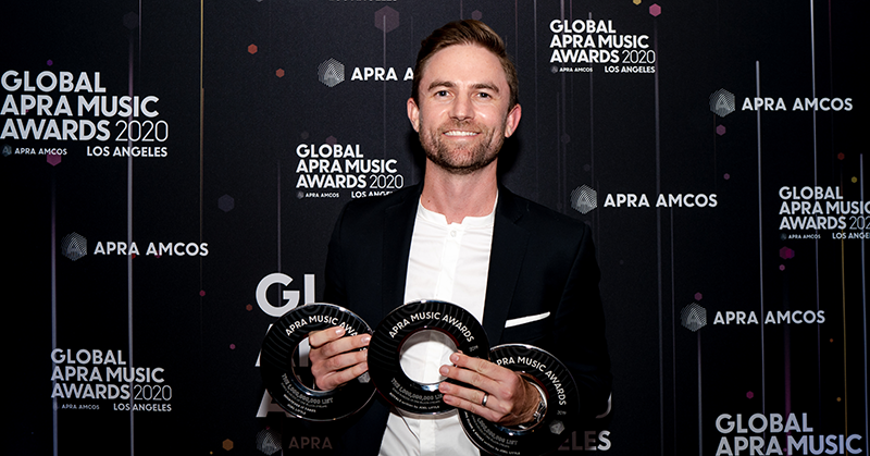 Joel Little stands at the media wall holding three black disk trophies