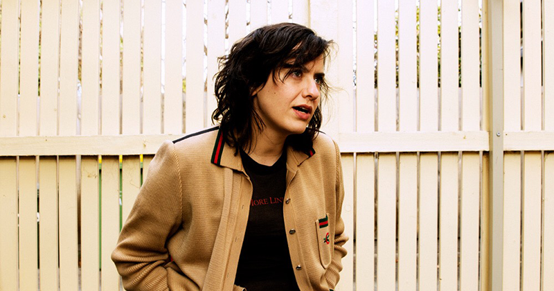 Laura Imbruglia wearing a brown jacket and black t-shirt stands in front of a white picket fence