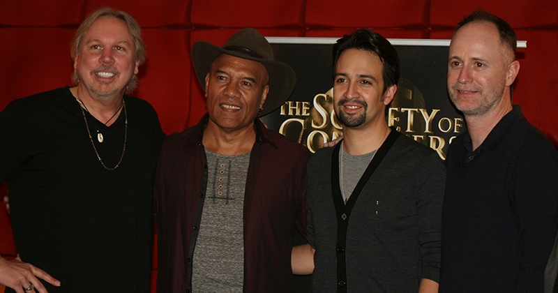 Mark Mancina, Opetaia Foa'i, Lin-Manuel Miranda and Tom MacDougall standing next to each other in front of a red wall