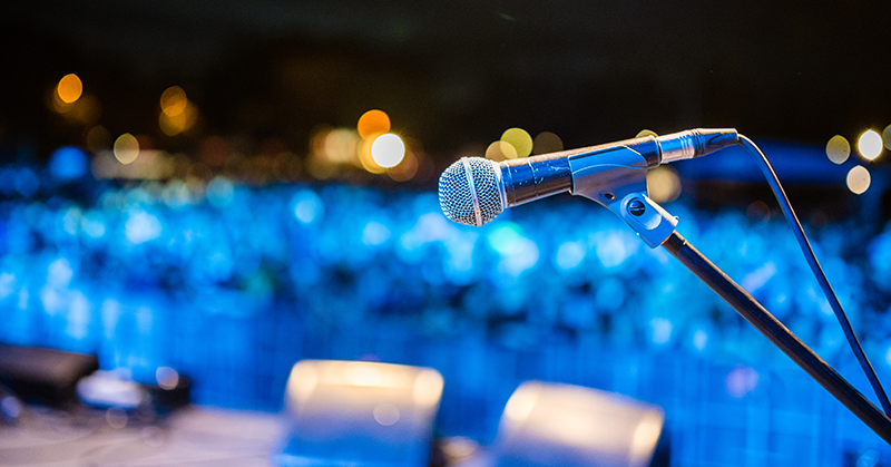 A microphone sits on a stage in blue light