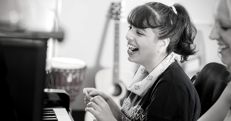 Young girl laughing as she sits in front of a piano