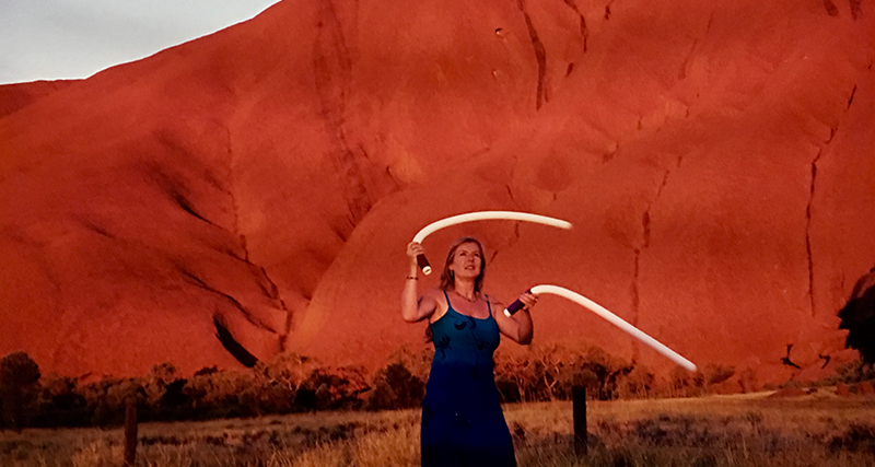 Sarah Hopkins stands in front of Uluru in Australia, holding two harmonic whirlies, a wind instrument she invented