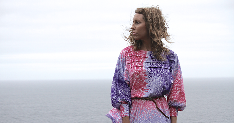 Sophie Hutchings wearing a pink and purple patterned dress looks out to sea