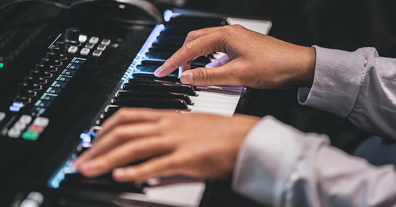 Hands playing keys on a black keyboard