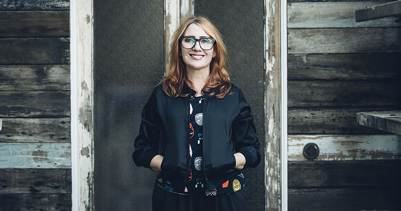 Viv Fantin stands in front of a wall with her hands in jacket pockets